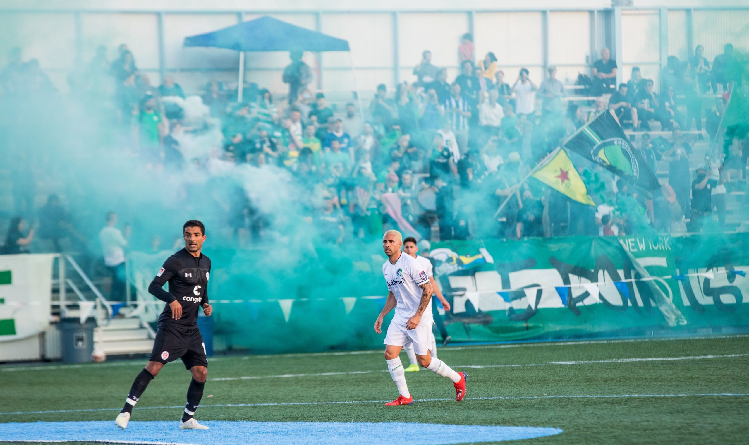 View from the field of a cosmos match with smoke and the YPG flag in the background.